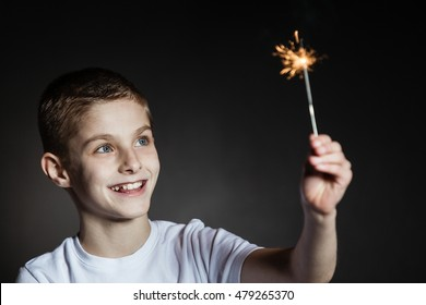 Amazed brown haired boy with blue eyes in white shirt holding lit sparkler