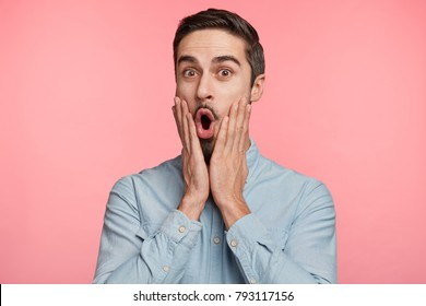 Amazed brunet male hears surprised news from friend, wonders about something, dressed formally, says: Wow, how great! Isolated shot of bearded young student expresses shock, poses on pink background