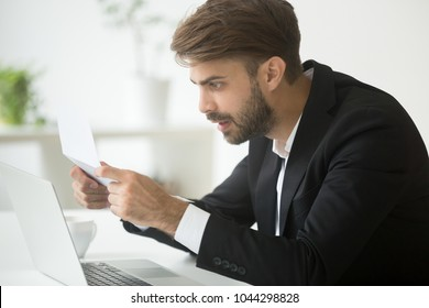 Amazed businessman in suit feeling shocked by reading mail, surprised entrepreneur stunned by unexpected loan rate increase in bank notice, confused employee astonished by unbelievable news in letter