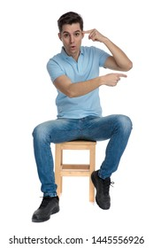 Amazed casual man pointing to his forehead and sideways while wearing a blue t-shirt and sitting on a chair on white studio background