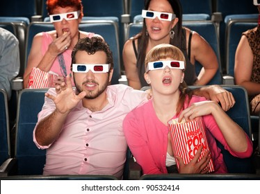 Amazed Caucasian couple with 3D glasses in theater seats