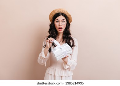 Amazed chinese girl opening gift. Studio shot of surprised asian woman with birthday present.