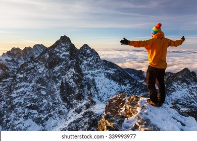 Amazed climber in colofrul jacket enjoys the breathtaking mountains views above clouds
