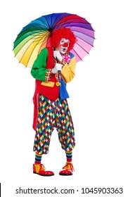 Amazed clown under rainbow umbrella full length picture against white background