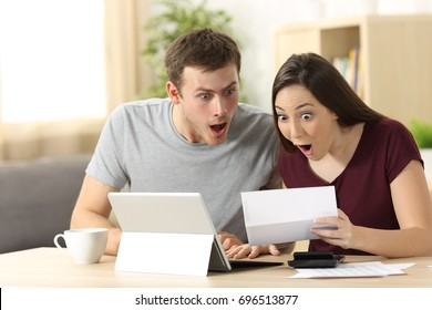 Amazed couple reading together a letter sitting in a desk at home