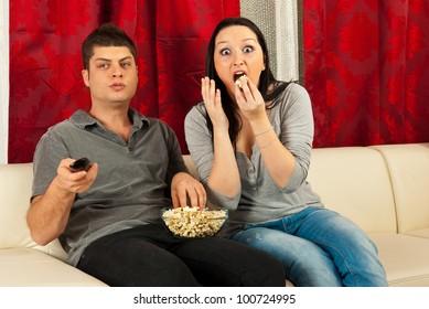 Amazed couple watching tv and eating popcorn