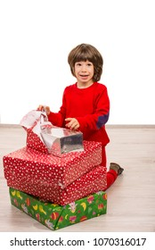 Amazed cute boy opeining Christmas gifts  and sitting on floor