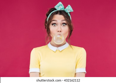 Amazed cute pinup girl in yellow dress blowing a bubble gum balloon over pink background
