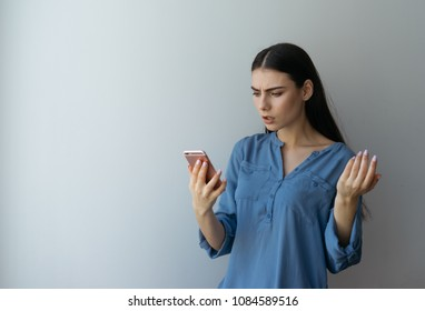 Amazed dissatisfied woman with brown hair, smartphone receiving message being shocked, to stare in screen at pink phone. Female finds true. anger and deceit. Beautiful young woman with blue eyes.