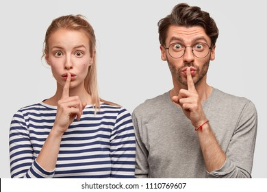 Amazed European female and male make silence sign, keep fore fingers on lips, tell secret and private information, isolated on white background. Surprised best friends gossip about something
