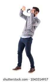 Amazed excited young adult man holding vr glasses and gesticulating with hand. Full body isolated on white studio background.