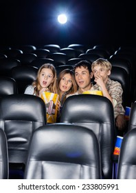 Amazed family of four watching movie in cinema theater