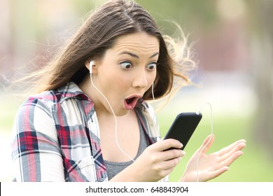 Amazed girl listening on line music and watching media content outdoors in a park