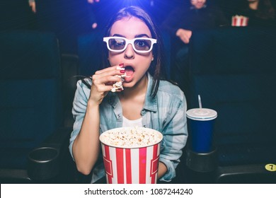 Amazed girl is sitting very close and looking straight. She wears special 3d glasses for watching movies. Girl is eating popcorn with her right hand. Also there is a cup of coke besides her.