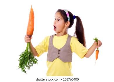 Amazed girl stands with two different sized carrots, isolated on white