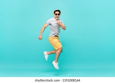 Amazed handsome Asian tourist man jumping studio shot isolated on light blue background