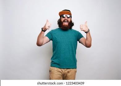 Amazed happy bearded man showing thumbs up