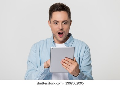 Amazed happy guy holding using digital tablet looking shocked about social media news, astonished man shopper consumer surprised excited by online win isolated on white grey blank studio background