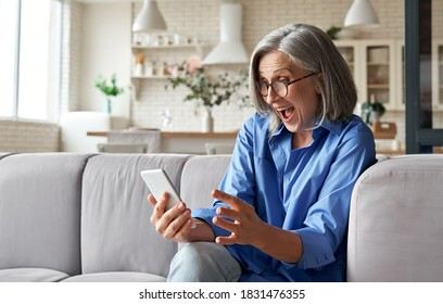 Amazed happy mature older 60s woman, excited customer holding smartphone using mobile app feeling great positive surprise reaction receiving gift reading sms on cell phone sitting on couch at home.