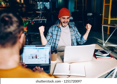 Amazed hipster guy feeling excited from received email with great news using laptop device in coworking office, back view of happy man satisfied with completed project screaming Yes as achievement