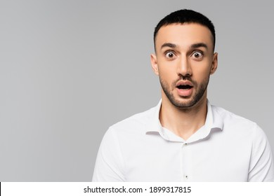 amazed hispanic manager with open mouth and bulging eyes looking at camera isolated on grey