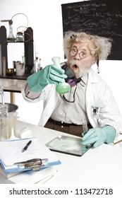 Amazed mad senior scientist in lab reacts to foaming green liquid overflowing beaker. Frizzy grey hair, round glasses, lab coat, aqua rubber gloves, blank blackboard, vertical, high key, copy space.