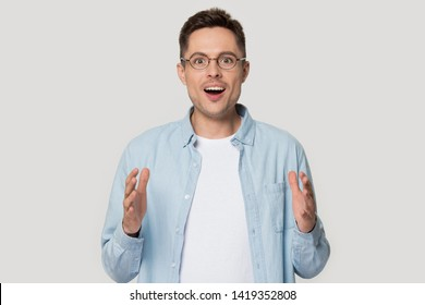 Amazed man in glasses look at camera show with hands large size feels shocked pose on grey wall, great offer big discount or ad of treatment penis enlargement increase length method and effectiveness
