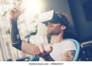 Amazed man looking in a VR goggles and gesturing