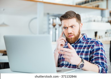 Amazed man talking on the phone and looking on laptop compter in coffee shop