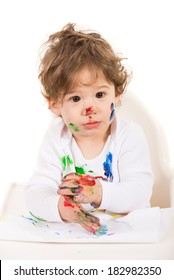 Amazed messy toddler boy with paints on his face and hands