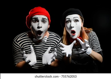 Amazed mimes with dropped jaws on black background. Male and female mime actors are dressed in striped shirts, white gloves and wearing artistic make-up.