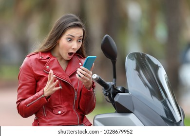 Amazed motorbiker reading exciting news on line in a smart phone on her motorbike