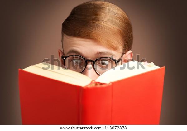 nerd asombrado leyendo un libro rojo con anteojos