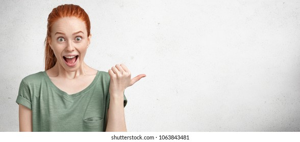 Amazed overjoyed beautiful red haired female looks with positive unexpected expression at camera, indicates at blank copy space for your promotional text or advertising content. Horizontal shot