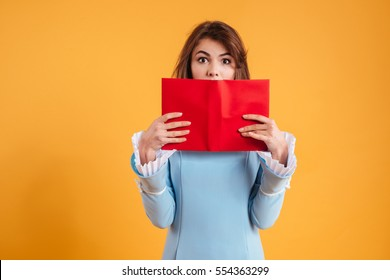 Amazed pretty young woman covered her face with red book