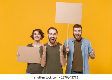Amazed protesting young three people guys girl hold protest signs broadsheet blank placard on stick spreading hands isolated on yellow background. Protests strikes pickets concept. Youth against city
