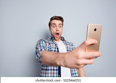 Amazed, scared guy in checkered shirt having, using smart phone, watching excited video through 3G, wi-fi internet, very impressed with wide open eyes and mouth over grey background