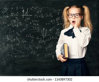 Amazed School Child Learning Math, Chalk Mathematics Formulas on Blackboard, Surprised Girl Kid with Book over Black Chalkboard