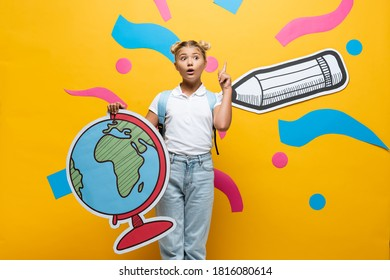amazed schoolgirl showing idea gesture while holding globe maquette near paper pencil and colorful elements on yellow