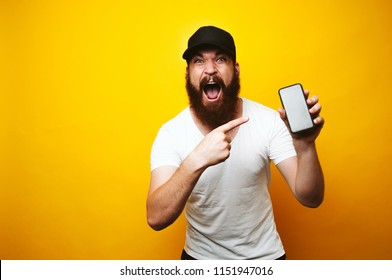 Amazed screaming young bearded man pointing at smartphone