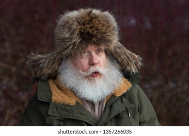 Amazed senior caucasian man with splendid mustache and beard against natural winter background. Portrait of elderly stylish hipster wearing a fur cap with tabs over the ears.