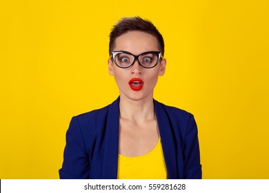 Amazed shocked business woman looking at camera open mouth isolated yellow background wall short hair blue formal suit shirt. Body language human emotion face expression studio shot horizontal image