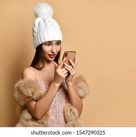 Amazed shocked wirth prices woman in shimmering silver dress, fur and winter hat choosing goods, online shopping, got bonus, cashback, discount on beige with free copy space