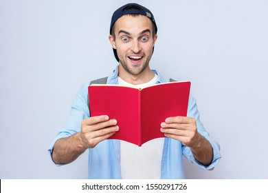 Amazed student guy with backpack reading a book, gray background