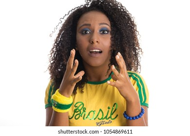Amazed, surprised. Brazil supporter. Brazilian woman fan celebrating on soccer / footbal match isolated on white background. Brazil colors.