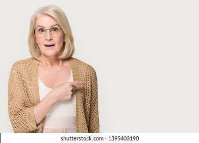 Amazed surprised positive senior woman wearing glasses knitted cardigan looking at camera pointing finger at copy free space advertisement announcement text eyewear store low prices good offer concept