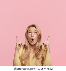 Amazed surprised woman with shocking expression indicates with fore fingers upwards, being stunned to notice something up, isolated over pink background. People, emotions and advertisment concept