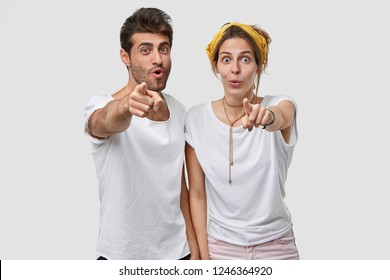 Amazed surprised young woman and man see something incredible, point directly at camera with index fingers, dressed in casual t shirt, isolated over white studio wall. Wow, look there, please