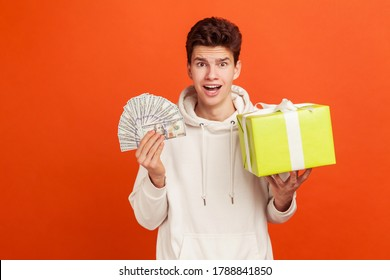 Amazed teenager in casual style white sweatshirt with hood holding lot of money and big yellow present box in hands, shocked with bonuses, giveaway. Indoor studio shot isolated on orange background