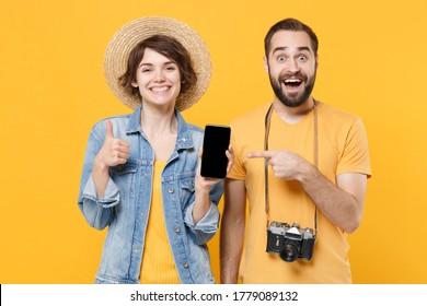 Touristes stupéfaits couple d'amis fille isolée sur fond jaune. Voyageur voyageant à l'étranger le week-end. Concept de vol aérien. Pointage sur un téléphone portable avec écran vide, affichage du pouce vers le haut